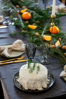 Pastel de navidad blanco sobre una mesa con ramas de pino