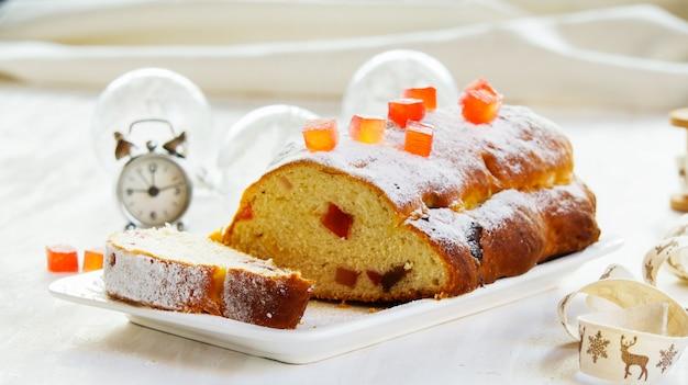 Pastel de navidad, decorado con azúcar en polvo, pastel de frutas en el fondo de piedra blanca