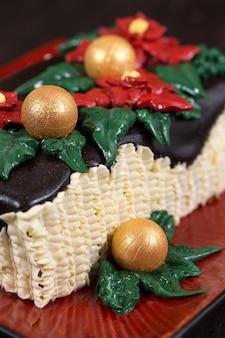 Pastel de navidad con flores de nochebuena rojas y bolas doradas