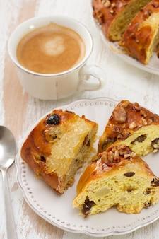 Pastel de navidad con frutos secos en plato blanco con taza de café