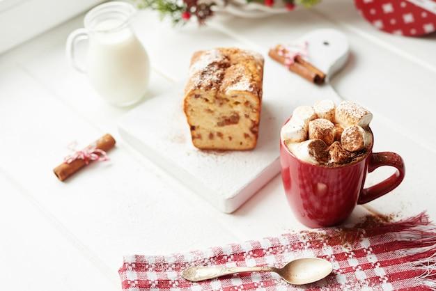 Pastel de navidad, leche, cacao con malvaviscos, canela junto a la ventana