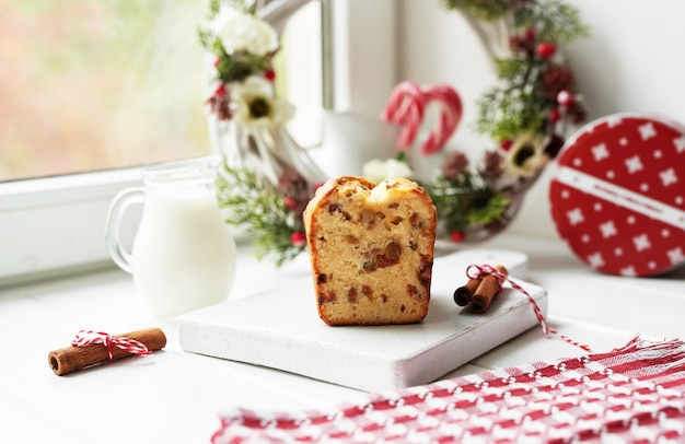 Pastel de navidad, leche, cacao con malvaviscos, canela en plato