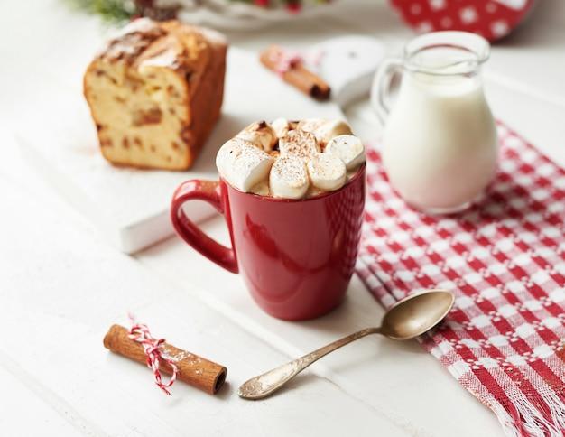 Pastel de navidad, leche, cacao con malvaviscos, canela sobre un blanco junto a la ventana