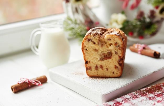 Pastel de navidad, leche, canela sobre un blanco junto a la ventana