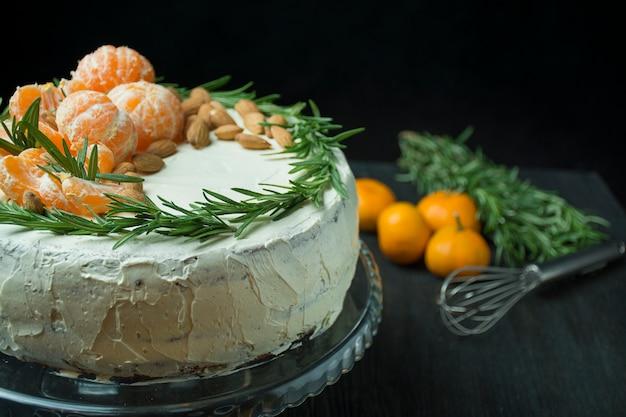 Pastel de navidad con mandarinas, almendras y romero en un stand. pastel de navidad con crema batida. mesa oscura espacio para texto.