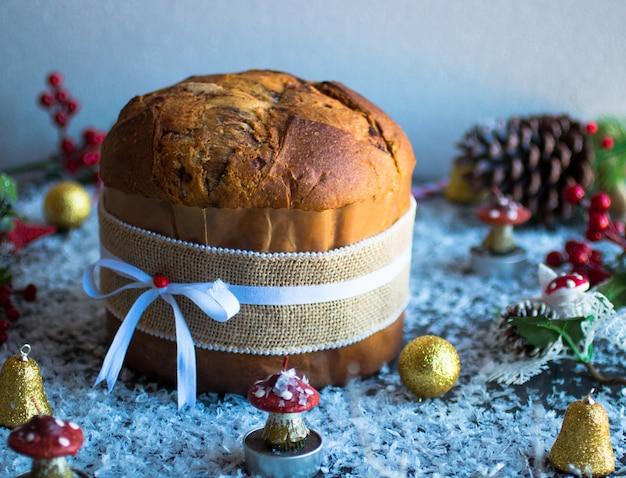 Pastel de navidad de panettone de chocolate italiano con adornos de adorno de velas conos de pino sobre un fondo de madera.
