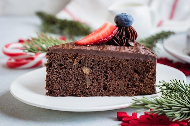 Pastel de navidad para postre. delicioso pedazo de pastel de chocolate con una taza de café y leche en la mesa de hormigón de piedra azul. concepto de comida de desayuno. decoración festiva de vacaciones