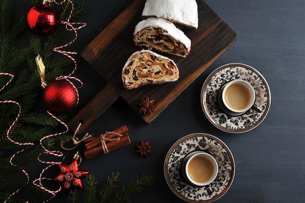 Pastel de navidad tradicional con pasas y nueces con ramas de árboles y juguetes, y dos tazas de café.
