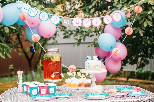 Pastel de niño o niña y diferentes golosinas para fiesta de baby shower en la mesa al aire libre