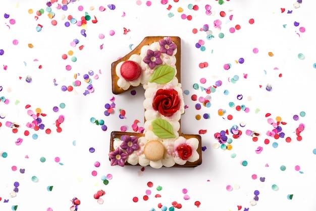 Pastel número uno decorado con flores, macarons y confeti aislado