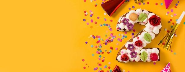 Pastel número dos decorado con flores, macarons y confeti aislado sobre fondo amarillo vista panorámica copia espacio