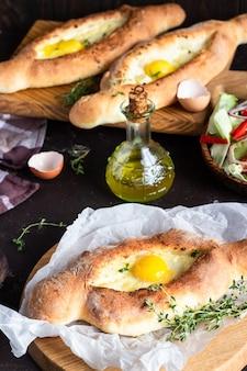 Pastel de pan abierto georgiano tradicional con queso y yema de huevo