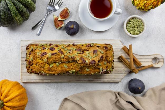 Pastel de pan de calabaza sobre una tabla de cortar de madera con nueces y semillas de calabaza sobre un fondo claro con calabazas e higos