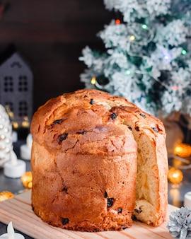 Pastel de panettone navideño con pasas y frutas confitadas con decoración navideña y velas