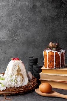 Pastel de pascua, kulich, flores y huevo sobre superficie negra