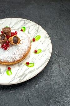 Un pastel un pastel con frutos rojos azúcar en polvo gofres de chocolate salsa verde