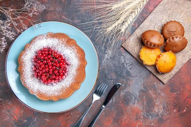 Un pastel un pastel con grosellas rojas cuchillo tenedor diferentes tipos de magdalenas