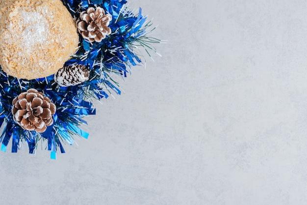 Pastel pequeño anidado en un paquete de adornos navideños sobre superficie de mármol