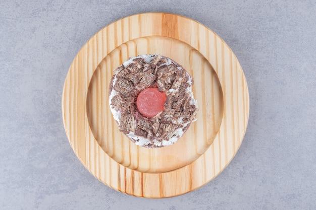 Pastel pequeño cubierto de crema en una bandeja de madera sobre una mesa de mármol.