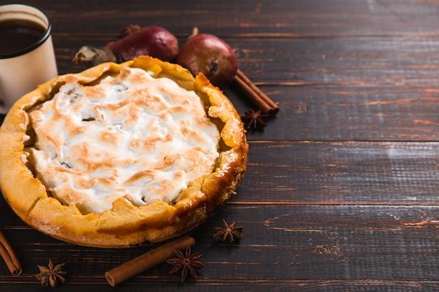 Pastel de pera con crema, pasteles caseros en la mesa de madera, café y especias. copie el espacio.