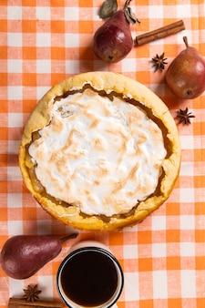 Pastel de pera con nata, repostería casera sobre la mesa con servilleta de naranja, café y especias. copie el espacio.