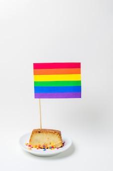 Pastel en plato con bandera de papel lgbt brillante con palo