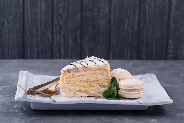 Pastel en plato con cubiertos y macarons