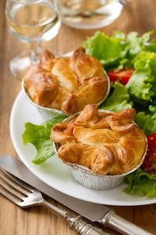 Pastel de pollo con ensalada en plato blanco sobre azul