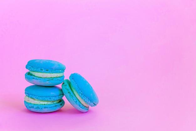 Pastel de postre macarrón o macarrón azul unicornio colorido de almendra dulce aislado sobre fondo rosa pastel de moda.