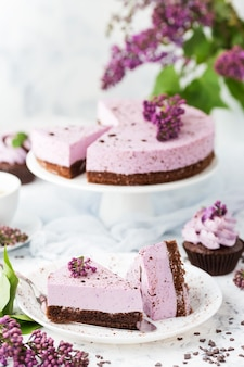 Pastel de queso de arándanos con galletas de chocolate decoradas con flores de color lila