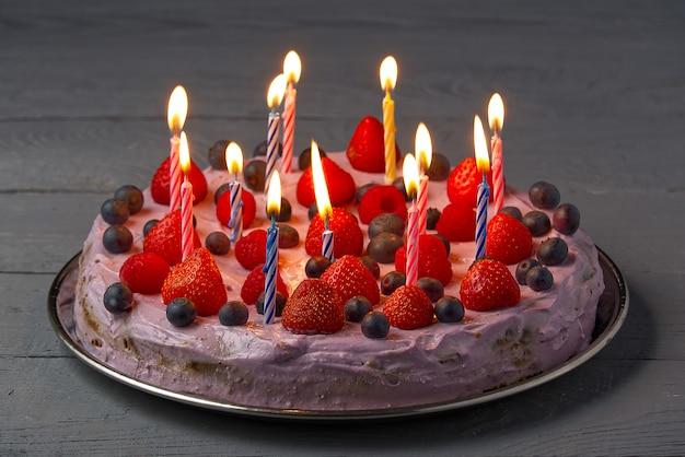 Pastel de queso de cumpleaños hecho en casa con bayas y velas de cumpleaños. tarta de queso con fresa, arándano y frambuesa.