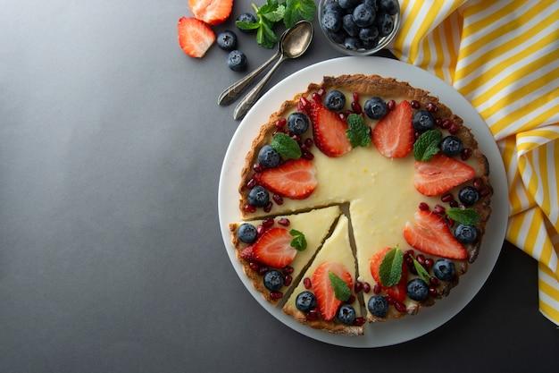 Pastel de queso entero con bayas frescas y menta para el postre. fondo gris