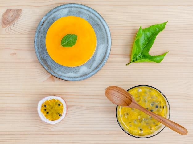 Pastel de queso de la fruta de la pasión con las hojas de menta fresca en fondo de madera.