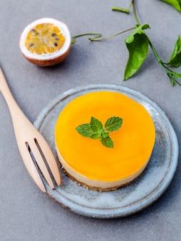 Pastel de queso de fruta de la pasión con hojas de menta fresca sobre fondo oscuro de hormigón.