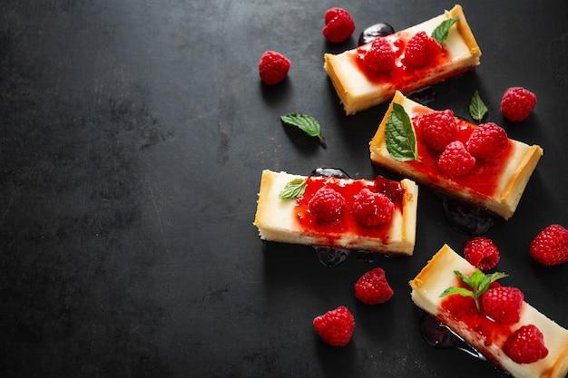 Pastel de queso servido con salsa y frambuesas.