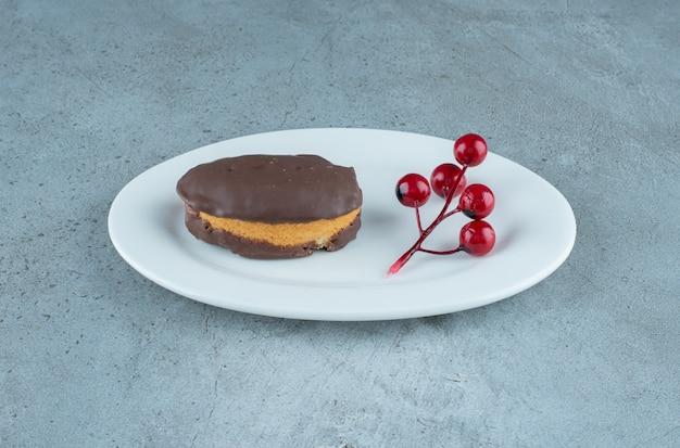 Pastel recubierto de chocolate y un racimo de bayas de navidad en un plato sobre fondo de mármol. foto de alta calidad