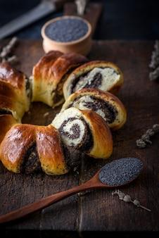 Pastel redondo al horno con semillas de amapola en una tabla de cortar de madera marrón