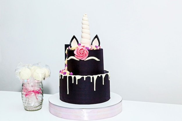 Pastel redondo de dos niveles en forma de unicornio sobre un fondo blanco.