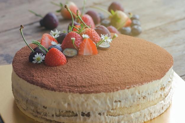 Pastel redondo de tiramisú en mesa de madera espolvoreado con polvo de cacao y decorado con frutas frescas