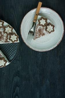 El pastel de requesón está decorado con galletas y chocolate negro rallado en madera oscura