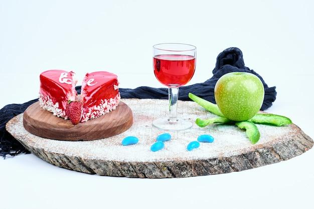 Un pastel rojo de san valentín con un vaso de bebida.