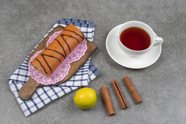 Pastel de rollo dulce, taza de té y palitos de canela en la superficie de mármol