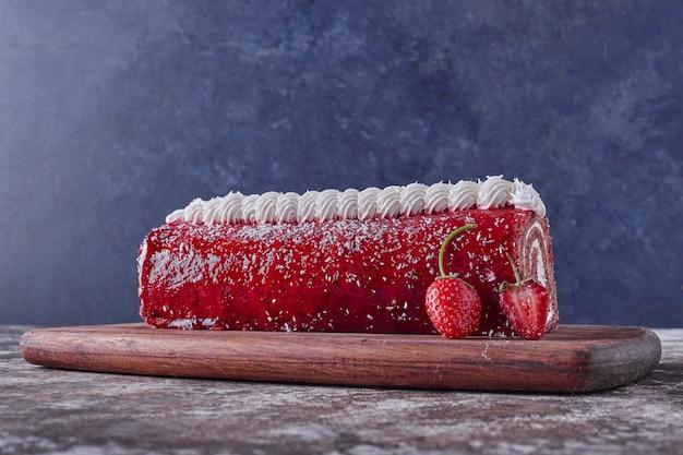 Pastel de rollo suizo con gelatina roja y crema blanca servido con fresas