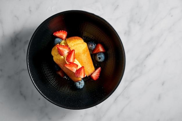 Pastel de ron baba con crema de mantequilla, rodajas de fresa y arándanos en una placa negra sobre una mesa de mármol blanco