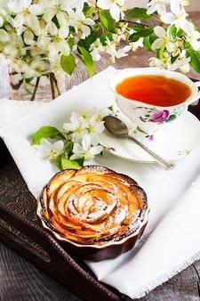 Pastel de rosas en forma de manzana y taza de té en la bandeja de servir