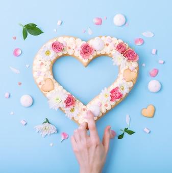 Pastel de san valentín en forma de corazón con flores como decoración.