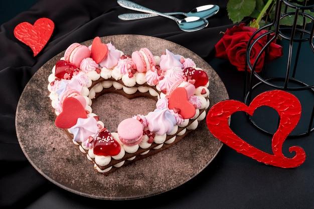 Pastel de san valentín en forma de corazón con rosa y plato