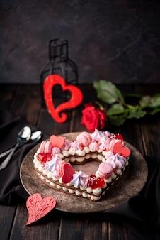 Pastel de san valentín en forma de corazón con rosas y cucharas