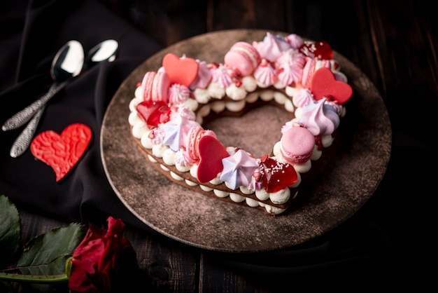 Pastel de san valentín en plato con corazones y rosa