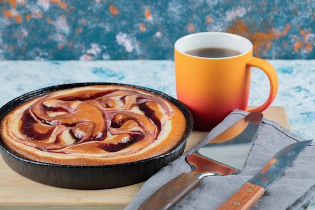 Pastel en una sartén negra con melocotón y una taza de té.